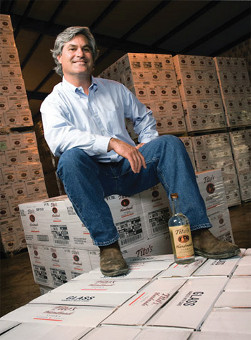Tito Beveridge sitting on boxes of Tito\'s Texas Vodka.